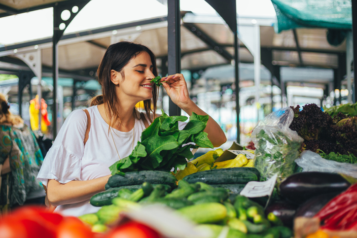 young woman smelling fresh basil at a farmers market