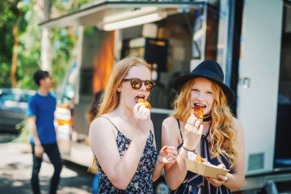 two redhead girls eating food from a food truck